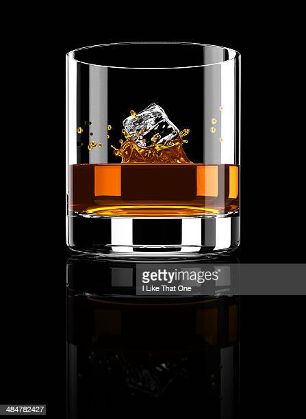 brandy / cognac tumbler with ice cube falling in - atomic imagery stock pictures, royalty-free photos & images