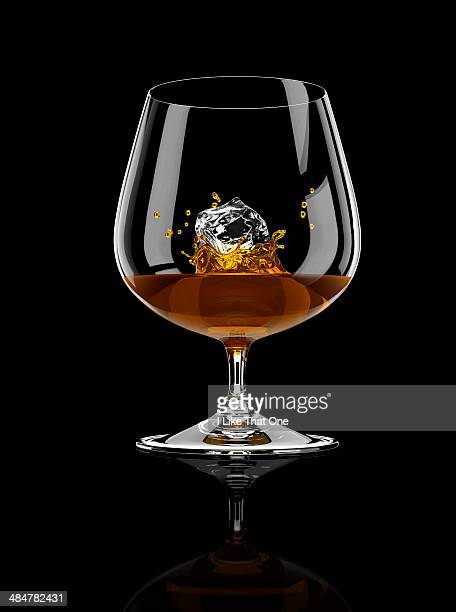 brandy / cognac with an ice cube - atomic imagery stock pictures, royalty-free photos & images
