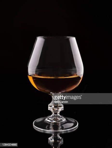 brandy glass on black background swirlin - cris cantón photography fotografías e imágenes de stock