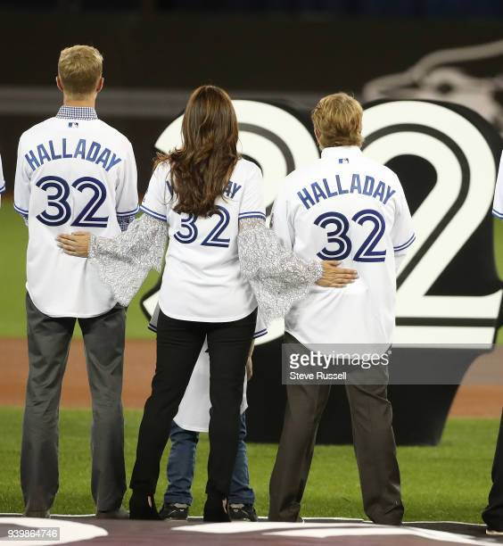 TORONTO ON MARCH 29 Brandy Halladay is flanked by her sons Braden and Ryan Halladay as the Jays retire Roy Doc Halladay's number 32 before the game...