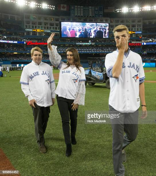 Brandy Halladaywaves to the crowd following the ceremony honouring her late husband Roy Doc Halladay On either side of Brandy are her sons Ryan and...