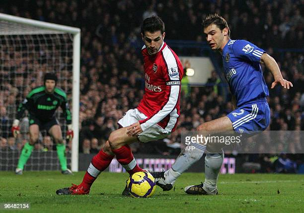 Branislav Ivanovic of Chelsea and Cesc Fabregas of Arsenal battle for the ball as Chelsea goalkeeper Petr Cech looks on during the English...
