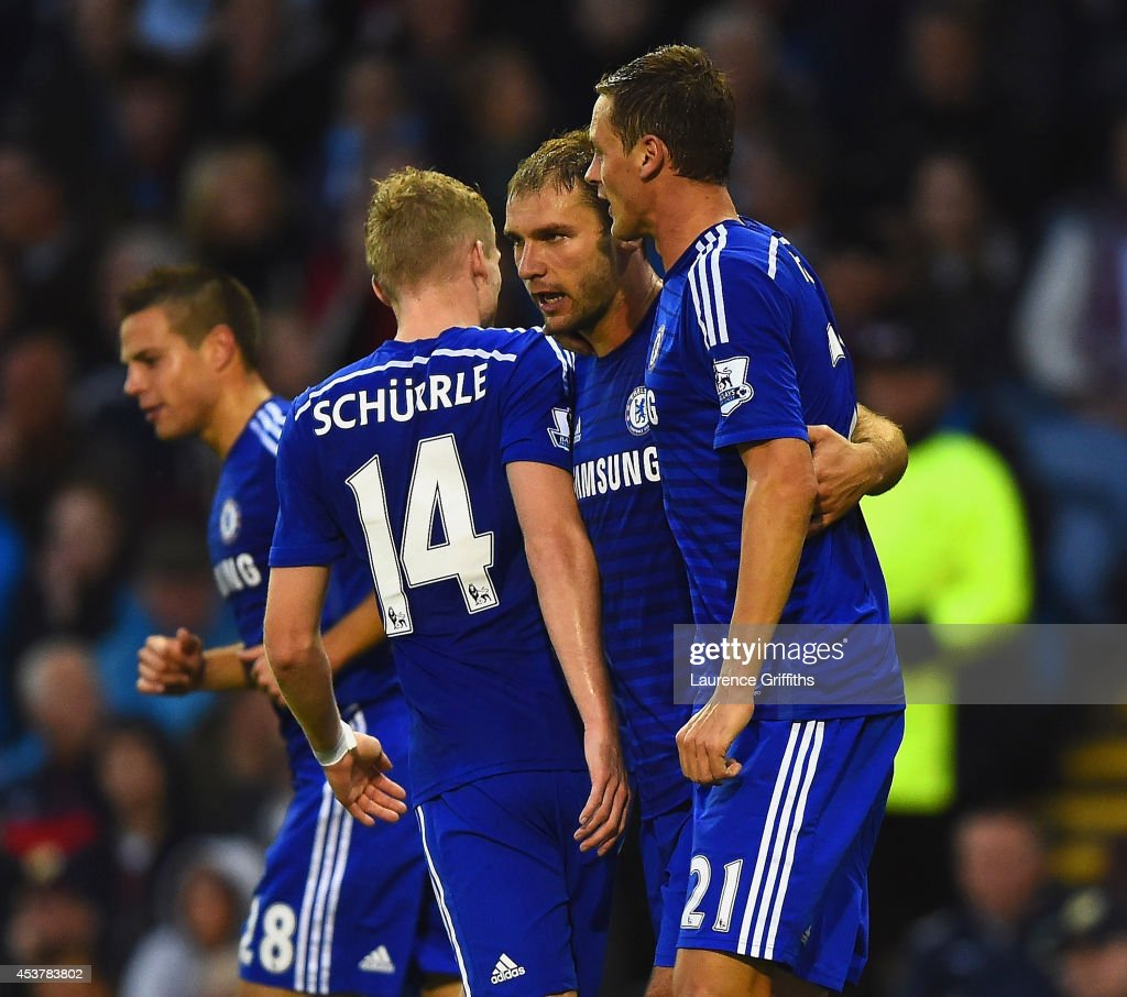 Branislav Ivanovic of Chelsea celebrates scoring their third goal with Andre Schurrle and Nemanja Matic of Chelsea during the Barclays Premier League match between Burnley and Chelsea at Turf Moor on August 18, 2014 in Burnley, England.