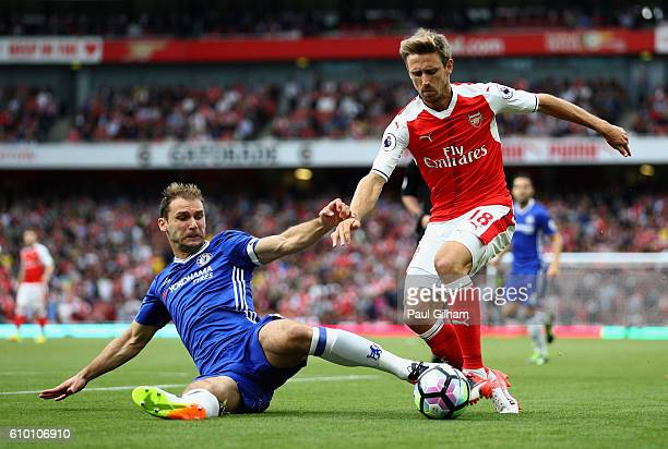 Branislav Ivanovic of Chelsea tackles Nacho Monreal of Arsenal during the Premier League match between Arsenal and Chelsea at the Emirates Stadium on...