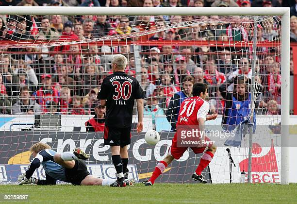 Branko Jelic of Cottbus scores the first goal as Goalkeeper Oliver Kahn and Christian Lell of Bayern Munich react during the Bundesliga match between...