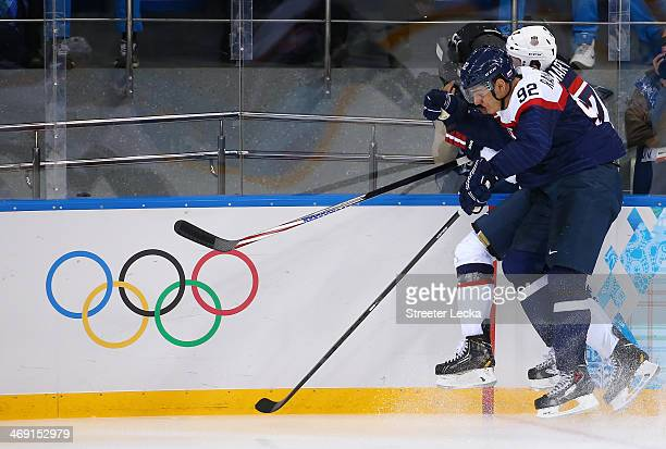 Branko Radivojevic of Slovakia and Paul Martin of United States battle for the puck during the Men's Ice Hockey Preliminary Round Group A game on day...