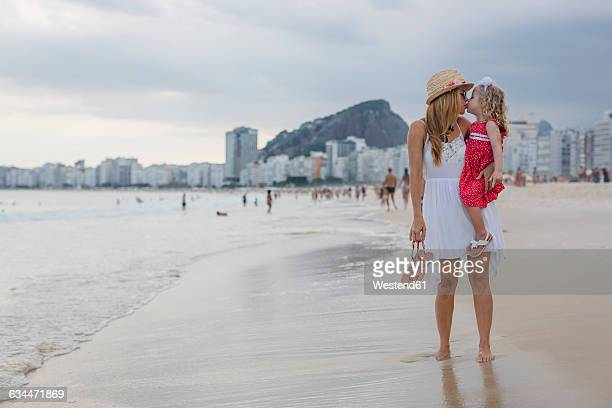 brasil, rio de janeiro, mother carrying and kissing daughter on copacabana beach - copacabana beach stock pictures, royalty-free photos & images