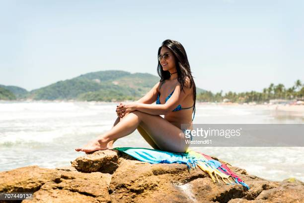 Brasil, Sao Paulo, Ubatuba, smiling young woman sitting on a rock at the beach