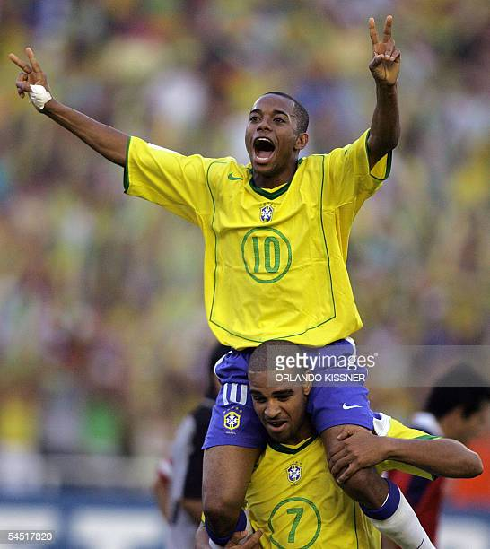 Brazilian striker Robinho is carried by forward Adriano celebrating Adriano's third goal against Chile during their South American qualifier match...