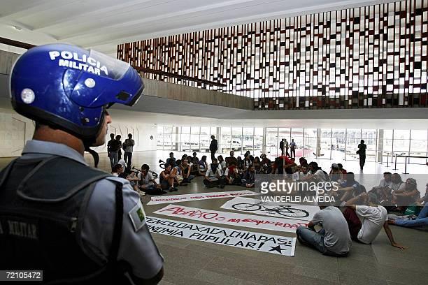 Un policia militar vigila a estudiantes brasilenos y mexicanos de la Red de Solidaridad con los Zapatistas, que se manifiestan contra la visita a...