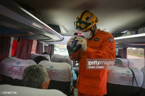 Brasilia firefighter uses a thermal camera and thermometer for passengers on a bus arriving in the city by the 040 road to avoid the spread of the...