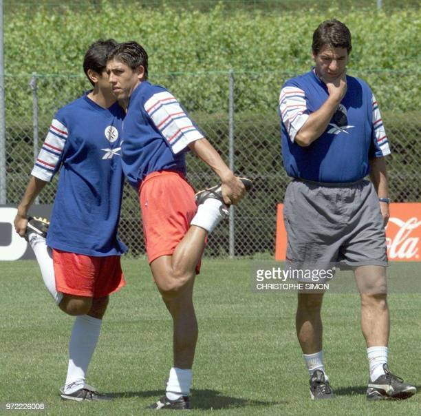 Brasilian coach of the Paraguayan soccer team Paulo Cesar Carpegiani , walks past Julio Cesar Enciso and unidentified player stretching during...