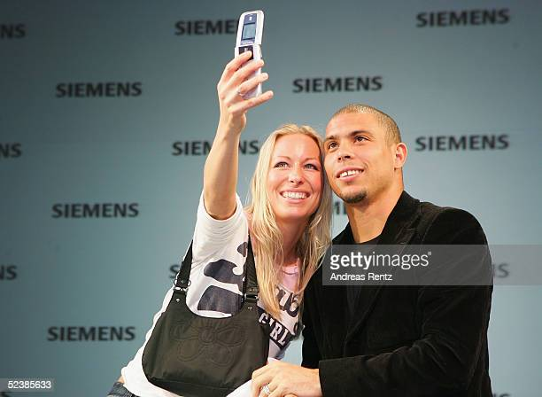 Brasilian football player, Ronaldo, poses with a young fan as she takes their picture with a camera phone at the CeBIT technology trade fair March...