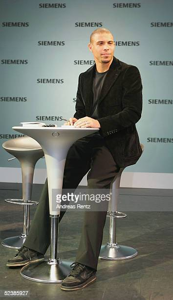 Brasilian football player Ronaldo sits at the Siemens mobile stand as he attends the CeBIT technology trade fair March 14 2005 in Hanover Germany...