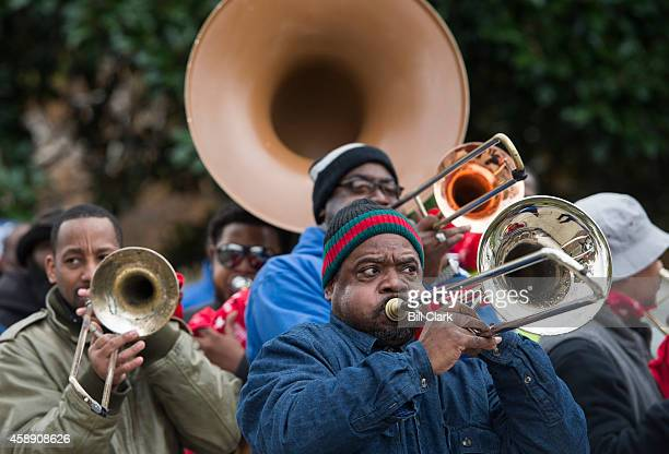 A brass band leads striking Federal Contract Workers as they march to the Capitol to call for higher wages on Thursday Nov 13 2014