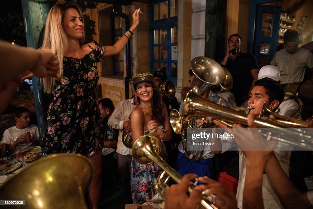 A brass band performs for revellers in a restaurant during the Guca Trumpet Festival on August 11, 2017 in Guca, Serbia. Thousands of revellers attend the trumpet festival, held annually since 1961 in the small, central Serbian town of Guca. The free event is a celebration of Balkan music with dozens of orchestras and solo trumpeters taking part in the festival's main competition. During the festival wild street parties take place throughout the night as brass bands parade and play for tips to the thousands of visitors in the town's restaurants, bars and pop-up tents.