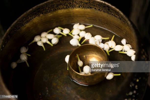 a brass bowl containing scented water and jasmine which thai people use to bath the buddha or song nam phra or elderly people - buddhist new year stock pictures, royalty-free photos & images