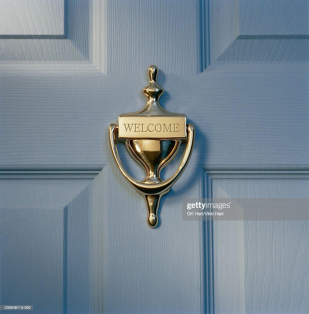 Brass door knocker on front door engraved with word 'welcome', close-up : Stock Photo