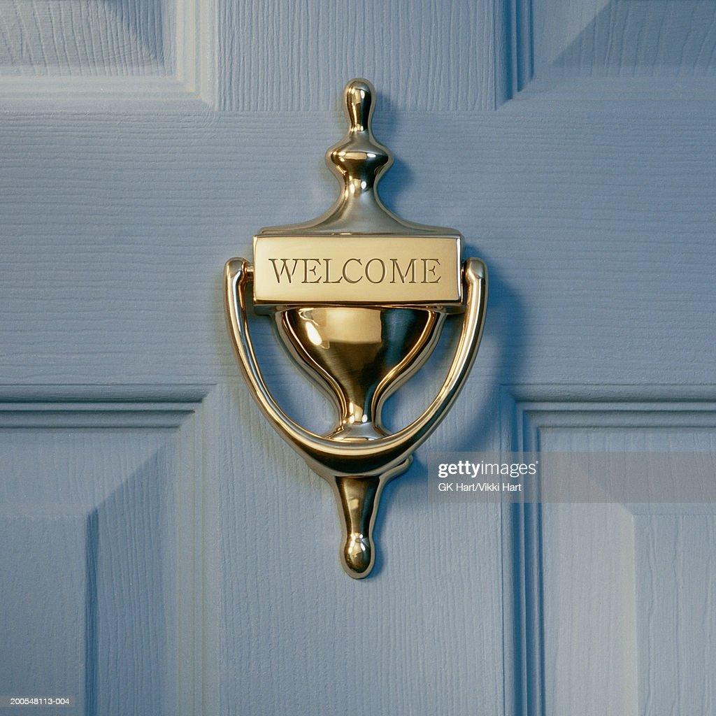 Brass door knocker on front door engraved with word welcome brass door knocker on front door engraved with word welcome close up rubansaba