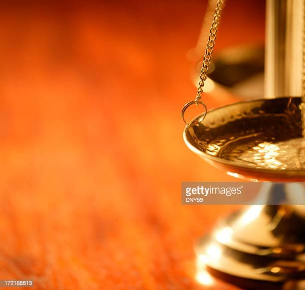 Brass justice scale on warm wooden table