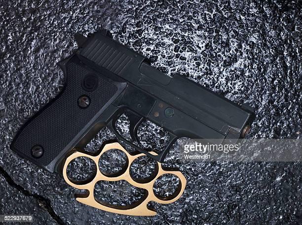 Brass knuckles and pistol on asphalt