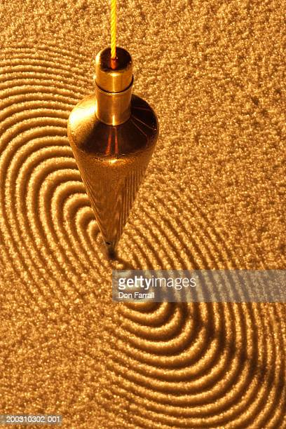 Brass pendulum making circle pattern in sand, elevated view
