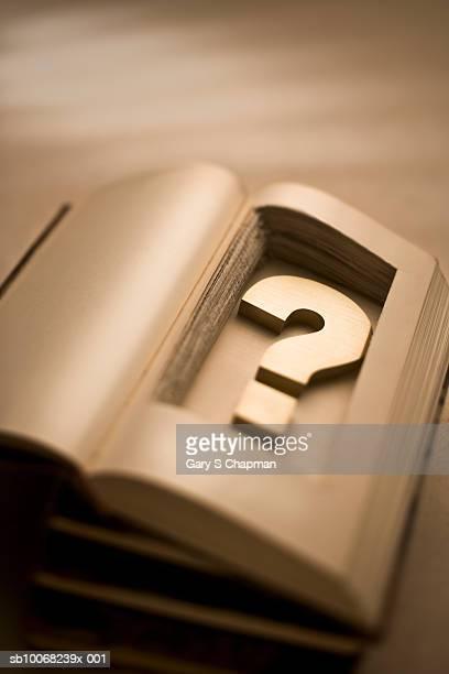 Brass question mark inside hollow book