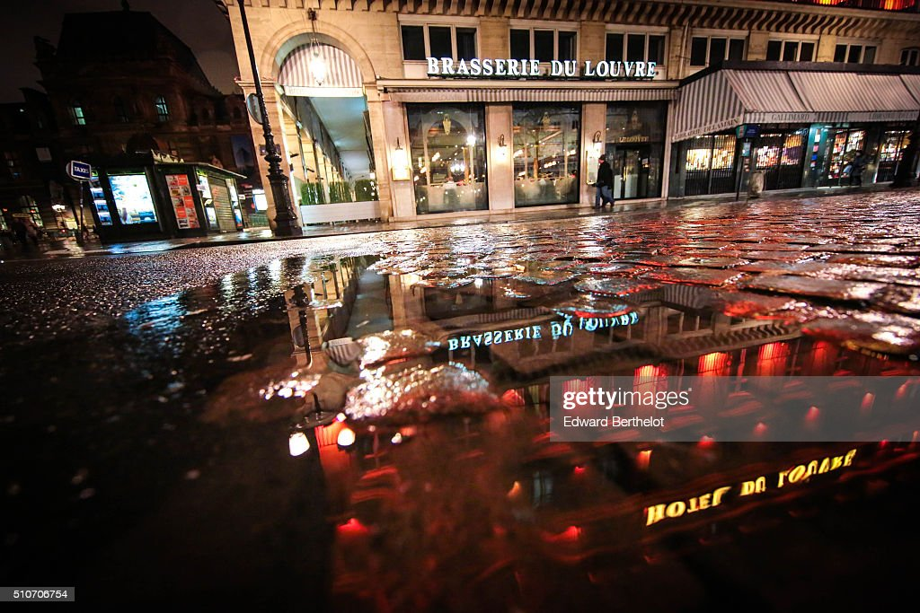 Brasserie du Louvre reflecting into a puddle on February 13, 2016 in the first quarter of Paris, France.