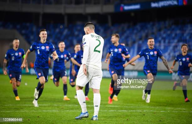 Bratislava , Slovakia - 8 October 2020; Matt Doherty of Republic of Ireland reacts after missing his penalty, as Slovakia players celebrate,...