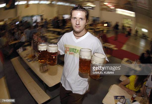 A waiter carries glasses of beer known as mass on the opening day of Slovakia's National Beer Festival in Bratislava 08 June 2007 AFP PHOTO/Samuel...