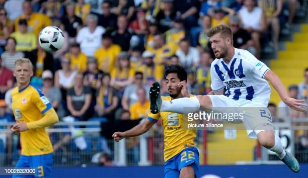 Braunschweig's Salim Khelifi and Karlsruhe's Yann Rolim vie for the ball during the German Bundesliga 2nd league soccer match between Eintracht...