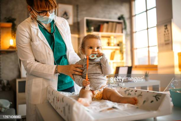 brave baby boy at doctor's office - baby changing mat stock pictures, royalty-free photos & images
