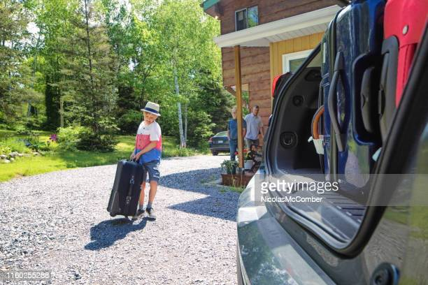 brave boy brings heavy luggage towards the car under the watch of his father - leaving stock pictures, royalty-free photos & images