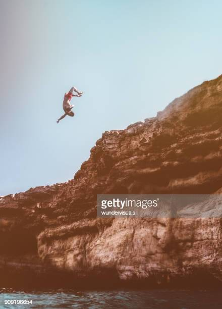 Brave cliff diver jumping off rock with somersault into sea