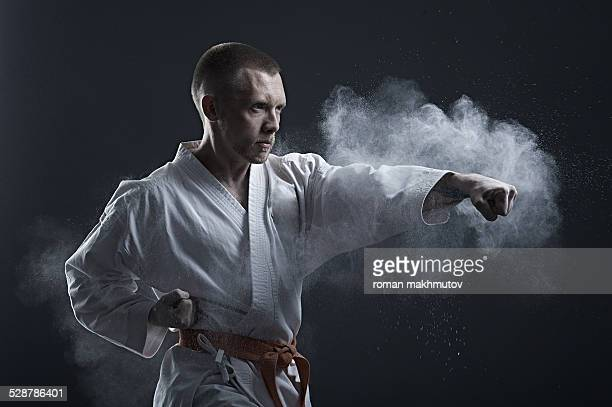 brave fighter in kimono doing karate - martial arts stock photos and pictures