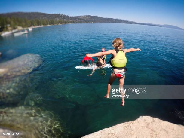brave girl jumping off rock to dad in the water - lake tahoe stock photos and pictures