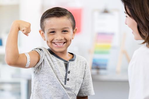 Brave little boy shows off arm bandage at pediatrician 1061308022