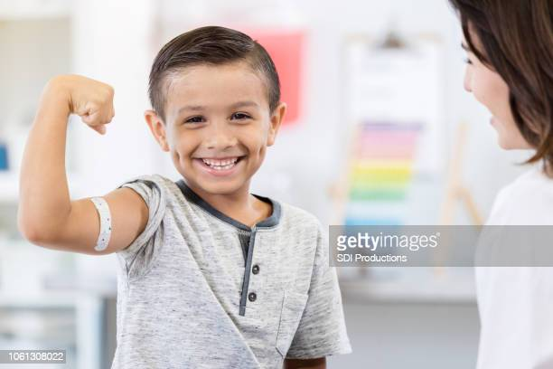 brave little boy shows off arm bandage at pediatrician - flexing muscles stock pictures, royalty-free photos & images