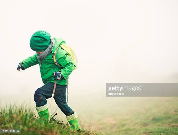 Brave little hiker climbing a hill in mist