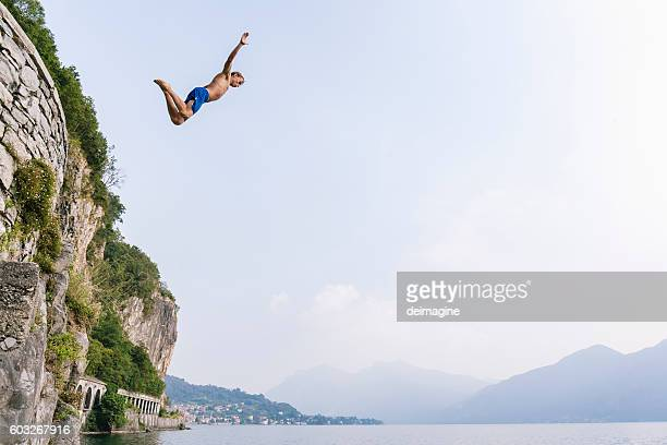 Brave man diving in the water from a cliff.