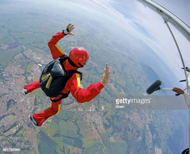 brave parachutist jumps out of an airplane in his red suit. - fallen soldier stock pictures, royalty-free photos & images