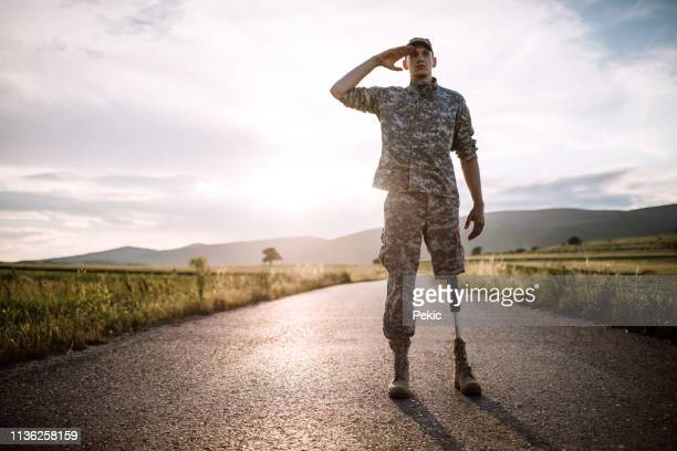 brave soldier with prosthetic leg saluting on road - saluting stock pictures, royalty-free photos & images