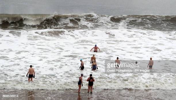 Brave swimmers from the Panama Swimming Club in Whitley Bay Tyne and Wear enter the North Sea for a dip as giant waves lash the shore Picture date...