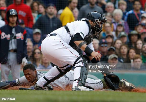 Braves Ronald Acuna Jr slides safely into home plate in front of Boston Red Sox catcher Sandy Leon during the fifth inning of a game between the...