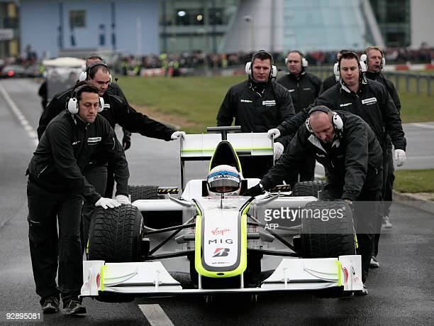 Brawn GP pit crew roll British Formula 1 test driver Anthony Davidson and his Brawn GP F1 car to the paddock at the Powered by MercedesBenz Live...
