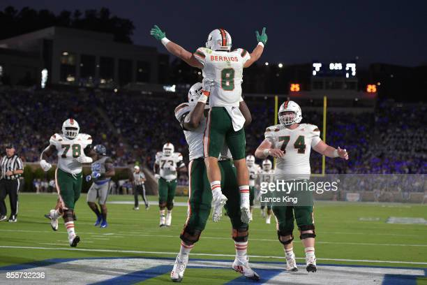 Braxton Berrios and Navaughn Donaldson of the Miami Hurricanes celebrate following a 27yard touchdown reception by Berrios during their game against...