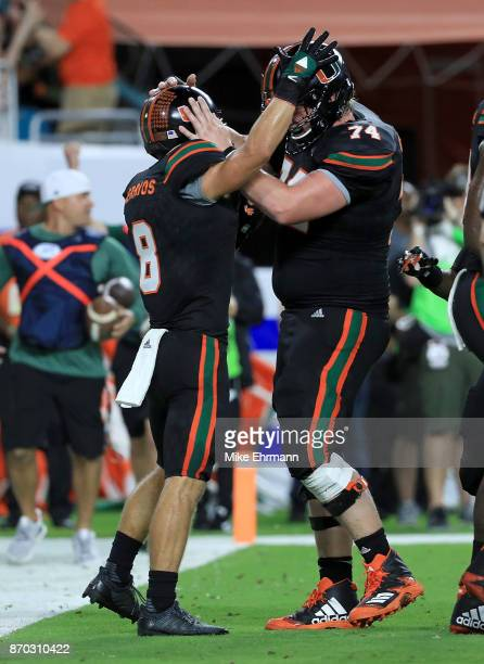 Braxton Berrios of the Miami Hurricanes celebrates a touchdown with Tyler Gauthier during a game against the Virginia Tech Hokies at Hard Rock...