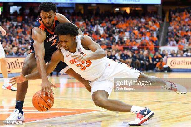 Braxton Key of the Virginia Cavaliers and Elijah Hughes of the Syracuse Orange battle for a loose ball during the second half at the Carrier Dome on...