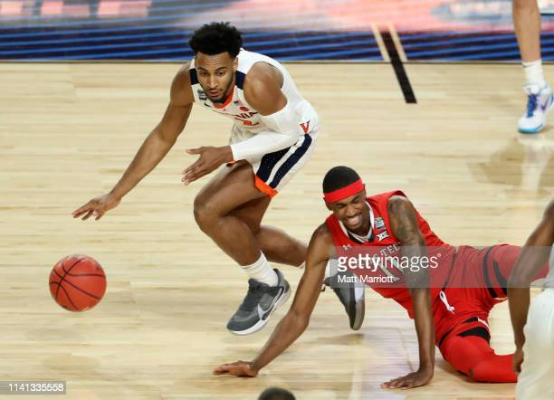 Braxton Key of the Virginia Cavaliers dribbles downcourt as Tariq Owens of the Texas Tech Red Raiders loses his footing during the first half in the...