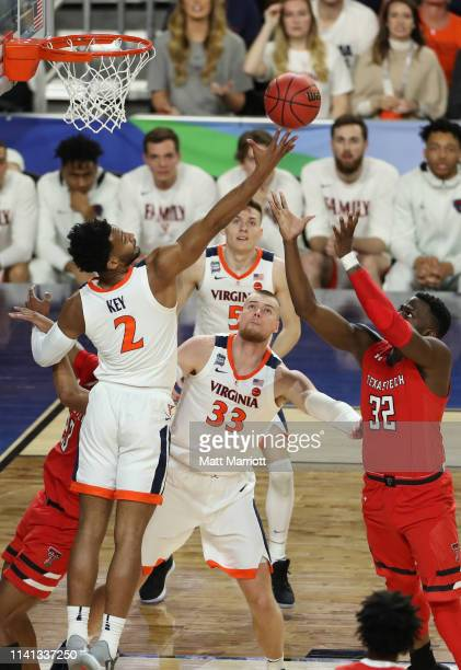 Braxton Key of the Virginia Cavaliers reaches for a loose ball against Norense Odiase of the Texas Tech Red Raiders during the first half in the 2019...